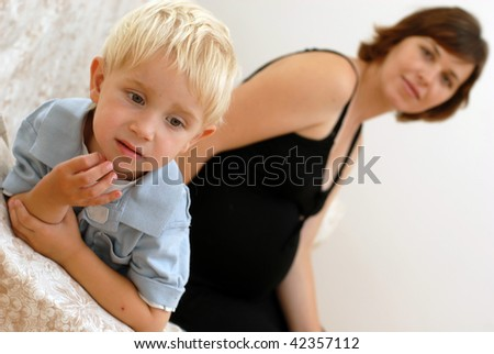 pregnant caucasian woman in black dress and little boy sitting on sofa