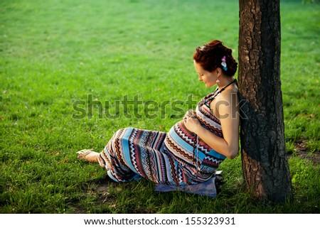 Pregnant caucasian woman takes rest outdoor - stock photo