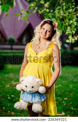 Pregnant caucasian woman takes rest outdoor. Pregnant woman posing in a green garden outdoor spring time. Outdoor portrait of beautiful pregnant woman holding her belly, nature background. - stock photo