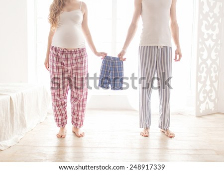 pregnant couple holding children's pajamas in the morning in the bedroom - stock photo