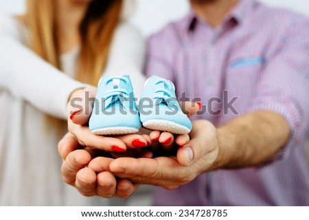 Pregnant couple holding their future baby boots - stock photo