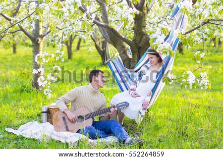 Pregnant couple in blooming garden at the picnic. Lazy time