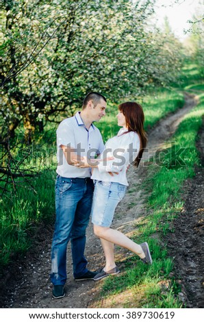 Pregnant couple in booming garden looking to each other