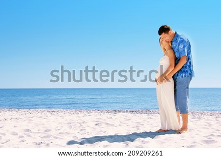 Pregnant couple in love on the beach - stock photo