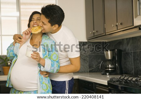Pregnant couple in pajamas in kitchen