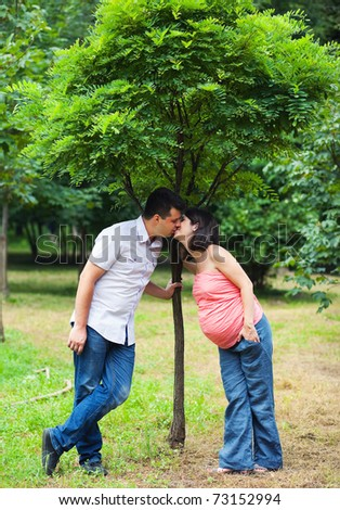 Pregnant couple kissing under young tree in park