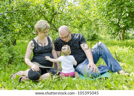 Pregnant couple with their one year old baby daughter - stock photo