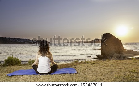 Pregnant doing yoga lotus position at seaside - stock photo