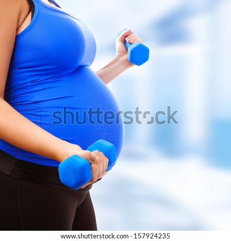 Pregnant female do exercise in sports hall, side view, body part, lifting dumbbells, active and sportive pregnancy, healthy motherhood concept - stock photo