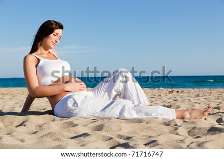 Pregnant female sitting on beach relaxing while vacation holding abdomen being joyful awaiting her newborn baby preparing for childbirth - stock photo