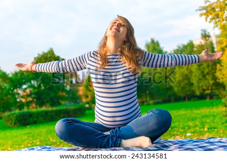 pregnant girl is preparing for the birth. doing breathing exercises on the nature - stock photo