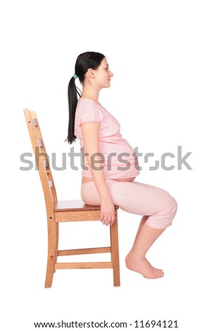 Pregnant girl sits on chair sideview