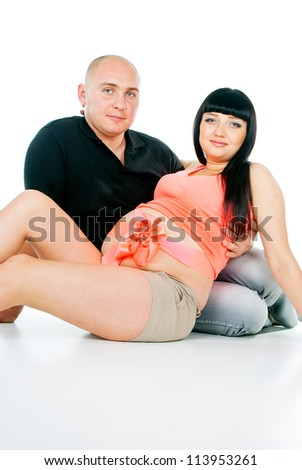 pregnant girl with a bow and her husband sitting - stock photo