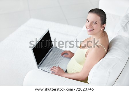 Pregnant girl with a laptop at home - stock photo