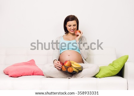 Pregnant happy smiling woman sitting on a sofa eating healthy food snack. Young beautiful mom expecting Baby. Pregnant Woman Belly. Maternity concept. Baby Shower - stock photo