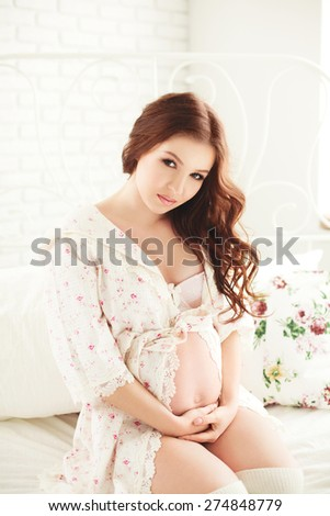 Pregnant Happy smiling Woman sitting on the bed in lace robe and caressing her belly. Mom Expecting Baby. Pregnant Woman Belly. Pregnancy. Beautiful Pregnant Woman. Maternity concept. Baby Shower - stock photo