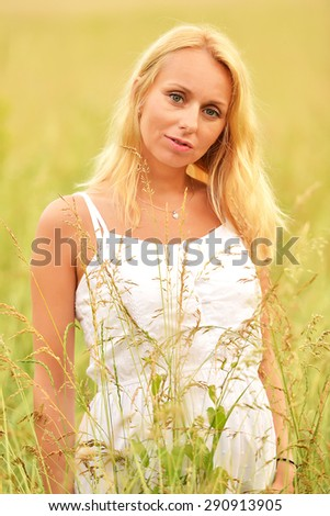 Pregnant happy woman in field outdoors - stock photo