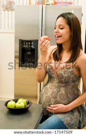 Pregnant Hispanic woman is eating a red apple in her kitchen.  Focus is on woman's face with background blurred. - stock photo