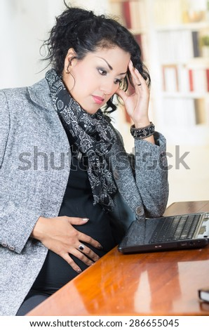 pregnant hispanic woman wearing casual clothes at work sitting at desk with thoughtful expression - stock photo