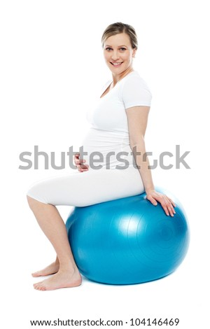 Pregnant lady sitting on exercise ball holding her belly