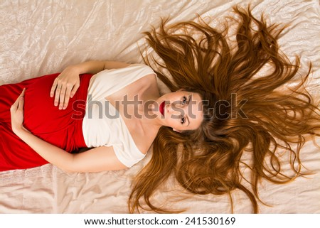 Pregnant lying on the bed and holding her stomach - stock photo