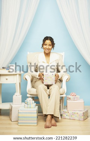 Pregnant Mixed Race woman holding gift - stock photo
