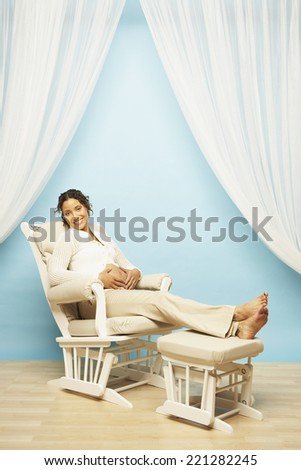 Pregnant Mixed Race woman sitting in rocking chair - stock photo