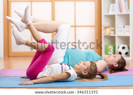 pregnant mom with first child doing gymnastics and fitness exercises - stock photo