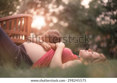 Pregnant Mother and Daughter Expecting Newborn Brother - stock photo