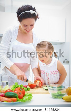 Pregnant mother and daughter in kitchen making a salad - stock photo