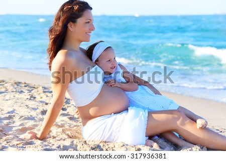 Pregnant mother and daughter on the beach together hug - stock photo