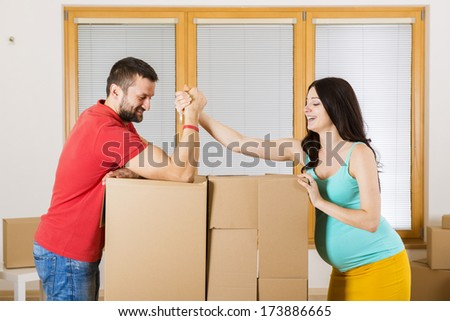 Pregnant mother and handsome father are going to move in to new house. Happy couple.
