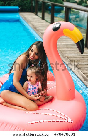 pregnant mother and her daughter was floating on an inflatable pink flamingos