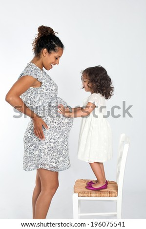 Pregnant mother and her little daughter - stock photo