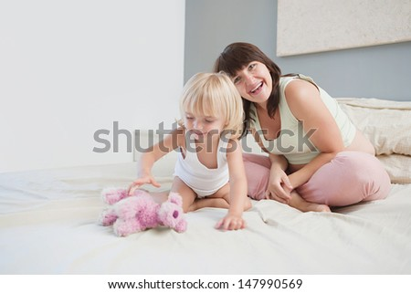Pregnant mother and young toddler daughter sitting on a bed at home being playful and having fun with a soft toy during the morning hours, interior.