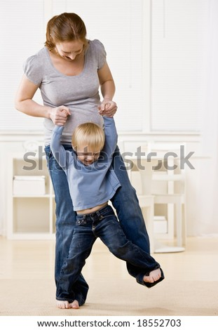 Pregnant mother dances playfully with her son on her feet - stock photo