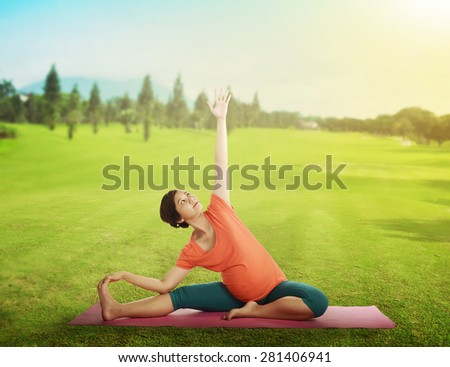 Pregnant mother doing yoga at the green grass in summer time - stock photo