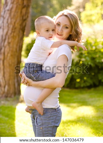 pregnant mother hugging her son - stock photo