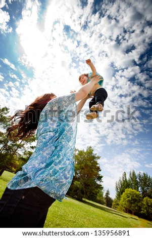 Pregnant mother in third trimester playing with her daughter in a park - stock photo
