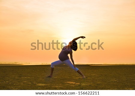 pregnant mother performing yoga on outdoor beach during sunset
