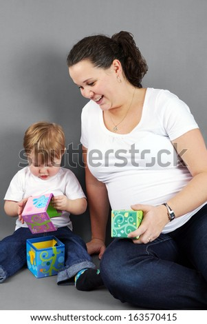 Pregnant mother playing with her little boy or toddler. - stock photo