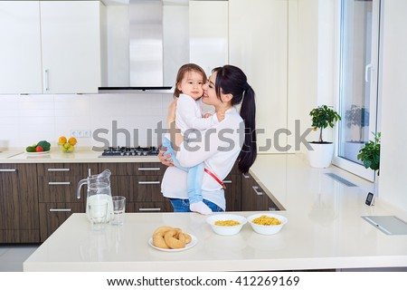 Pregnant mother playing with toddler daughter on the kitchen - stock photo