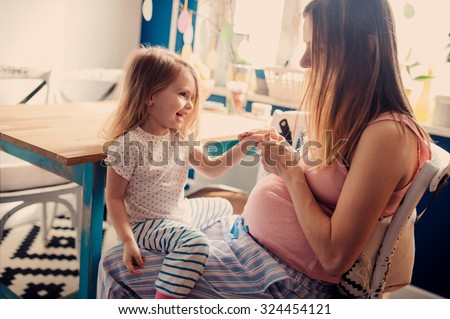 pregnant mother playing with toddler daughter on the kitchen, real life interior lifestyle - stock photo