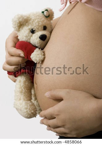 Pregnant mother showing her belly and holding a teddy