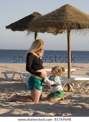 Pregnant mother with daughter  on the beach wearing sunglasses - stock photo