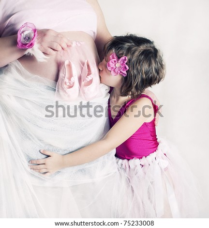 Pregnant mother with her daughter - stock photo