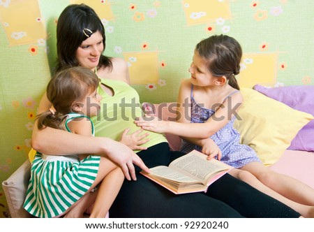 Pregnant mum with two daughters, an interior - stock photo
