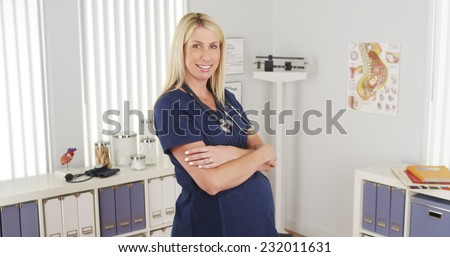 Pregnant nurse smiling - stock photo