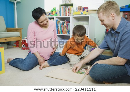 Pregnant parents playing with young son - stock photo