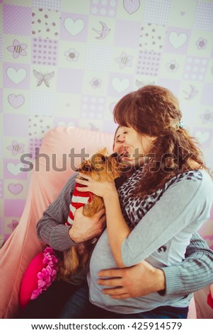 Pregnant wife tries to kiss her little dog - stock photo